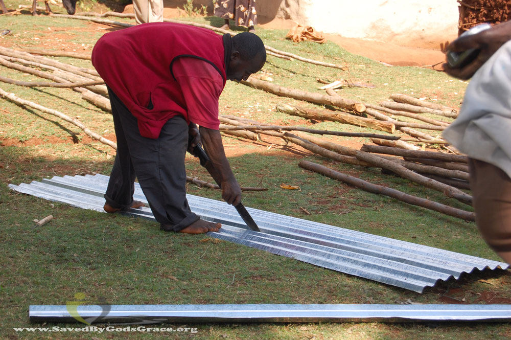 cutting-tin-sheets-with-machete-barefoot